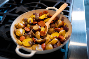 handmade wooden spoon in staub pan on stove - Earlywood