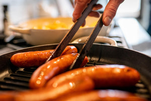 rotating brats with wooden cooking tongs by earlywood