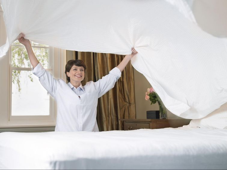 woman putting on freshly cleaned bed sheets