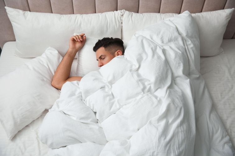 person sleeping in clean bedsheets