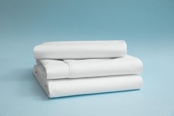 A stack of neatly folded white bamboo rayon bedsheets