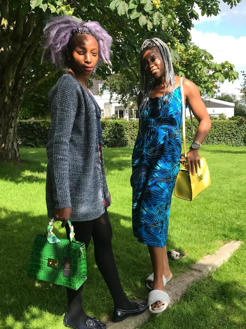 Two ladies in park holding Green and Yellow Crocodile embossed leather bags
