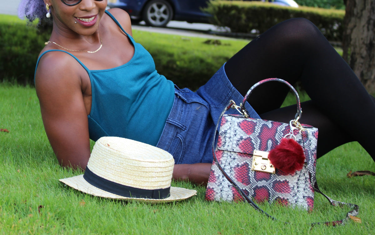 Red snake embossed leather bag with model laying on grass