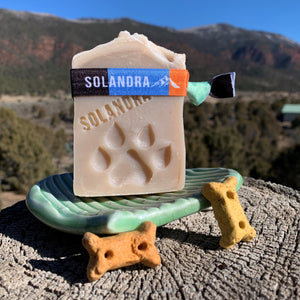 Dog Soap with dog paw stamped into the soap sitting on a ceramic green soap dish on a log with little dog bones and mountain background.