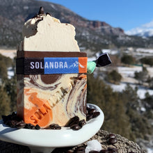 Load image into Gallery viewer, Java Orange Soap with swirls of orange, brown & cream.  Fresh ground coffee and coffee beans on top.  Soap is sitting on an artisan white ceramic soap dish with light snowy fields, hills and mountains.