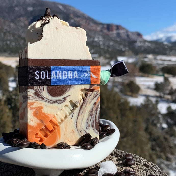 Java Orange Soap with swirls of orange, brown & cream.  Fresh ground coffee and coffee beans on top.  Soap is sitting on an artisan white ceramic soap dish with light snowy fields, hills and mountains.