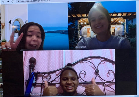Three teen girls smiling over video chat.