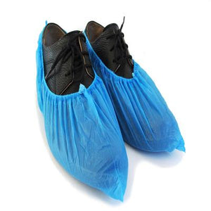 Pair of blue disposable overshoes on top of black shoes