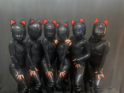 Six women in black latex bodysuits and black cat helmets standing in a row