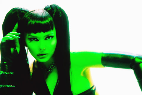 Woman with black hair and pigtails looking at the camera wearing black Vex opera knuckle gloves with green front lighting