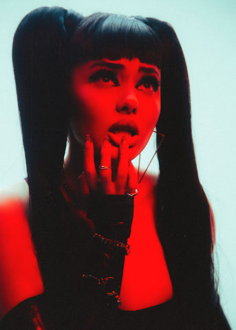 Woman with black hair in pigtails posing looking away from the camera  wearing black Vex  opera knuckle gloves and red front lighting