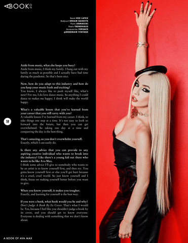 Ava Max wearing black Vex Mini Beret with black pants and top standing against a red wall for A Book Of Magazine