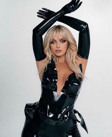 Bebe Rexha wearing custom black Vex bodysuit with black opera gloves. Posing with arms crossed over her head against a white wall.