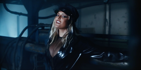 Artist Bebe Rexha walking through a wearing house wearing a black Vex trench and hat for her music video