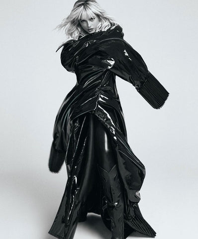 Bebe Rexha wearing oversized black latex outfit and Vex high waisted leggings underneath, image in black and white against a white wall