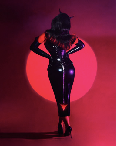 Christina Aguilera looking back-words with an hourglass shape. Wearing a black latex corset dress and chain devil tail.