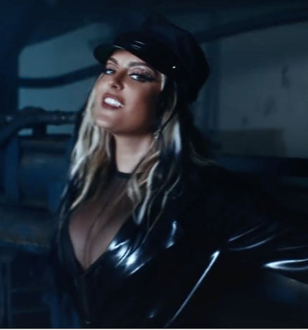 Musical Artist Bebe Rexha wearing a black latex trench coat and hat in a warehouse style setting for her music video