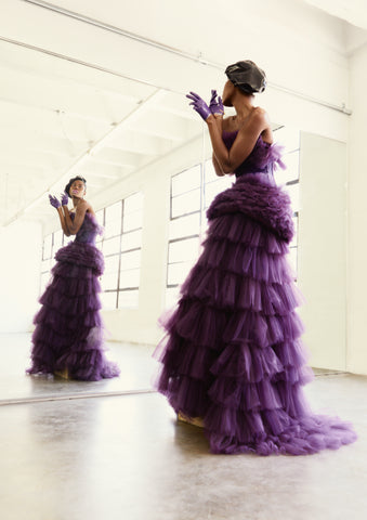 Model in Faddy Magazine wearing a black Vex Latex Beret and purple flowing gown standing in front of a wall mirror