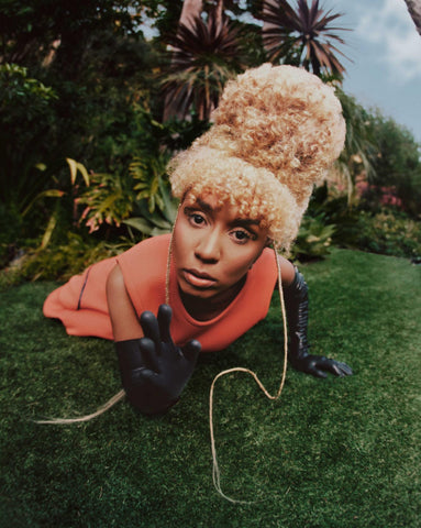 Woman laying in the grass with an orange dress and Vex black latex opera gloves posing for a photoshoot