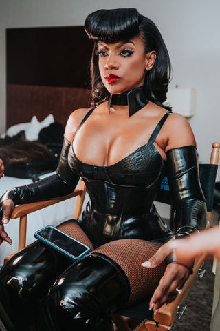 Kandi Burruss wearing black latex dungeon look with pin up style hair sitting in a chair getting ready