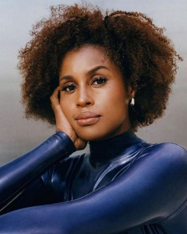 Actress Issa Rae posing thoughtfully in the long sleeved Vex Blair Bodysuit in navy