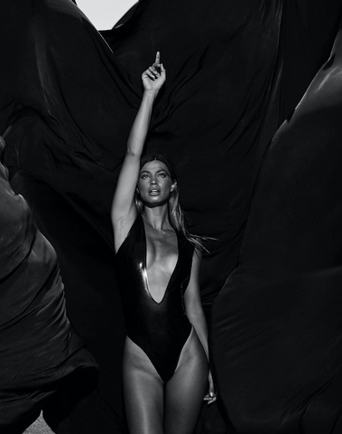Model Maggie Rawlins wearing a plunging black Vex Custom Bodysuit pointing up for Modeliste Magaz