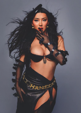 Nikita Dragun wearing a black Vex Mini Beret with a black bra, skirt and gloves held up to her lips in the winter 2020 issue of Interview Magazine