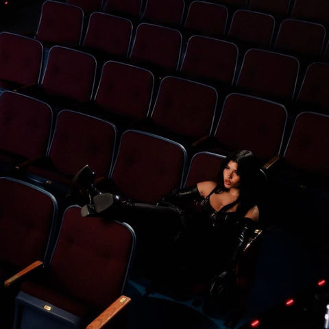 Musician wearing a black Vex spiked bra sitting in a movie theater for her music video
