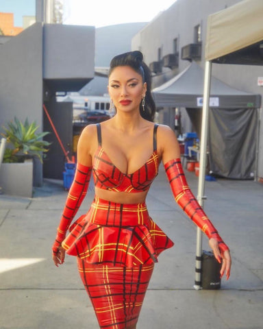 Nicole Scherzinger wearing a red, white and black plaid bra, skirt and gloves on set for the Masked Singer