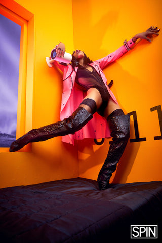 Rico Nasty wearing Vex custom pink spike trench, tall black snake print boots and black body suit for a photoshoot posing leaned back against an orange wall