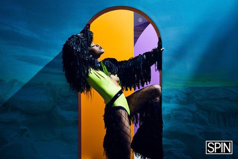 Rico nasty wearing neon green deep v Vex body suit with mesh tights, matching black fringed chaps and bolero with green hair for a photoshoot posing again multicolored walls