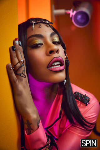 Rico Nasty wearing Vex custom pink spike trench for a photoshoot posing close up with full makeup and pink lips against an orange wall