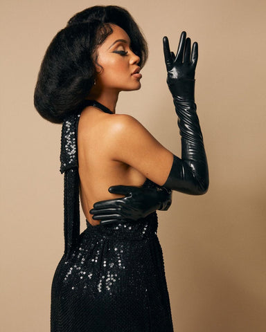 Recording artist Saweetie wearing a long black gown with black latex Vex opera gloves posing side profile against a tan wall for W Magazine