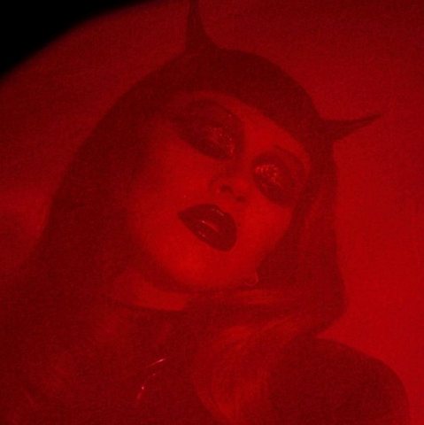 Christina Aguilera with closed eyes wearing latex devil horns.