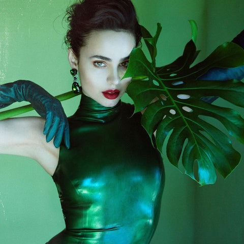 Actress Sofia Carson wearing Vex's green halter bodysuit and green gloves posing against a green background next to a plant with red lipstick