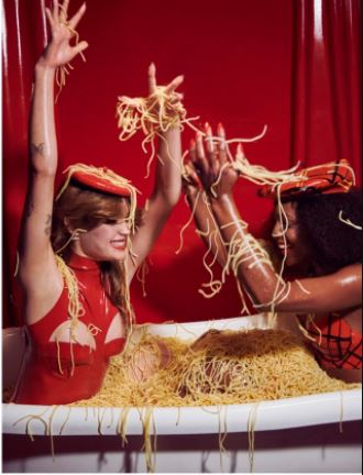 Two models in a bathtub of spaghetti wearing a red Vex mini beret and red divide bodysuit with a red backdrop