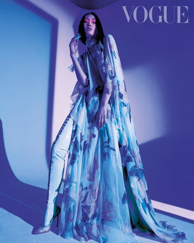 Model for Vogue Taiwan wearing blue vex clip leggings with a blue floral gown against a blue filtered backdrop