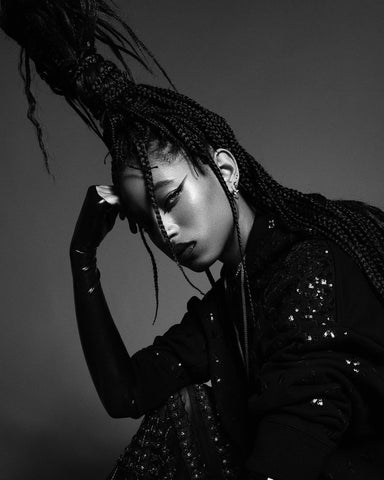 Willow Smith posing in a black and with photo with a high pony and black knuckle gloves