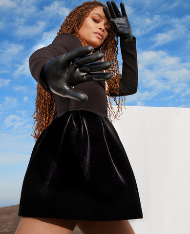 Woman wearing a black skirt and top with Vex's black wristlet gloves featured in Shape Magazine