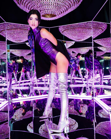 Celebrity feature wearing the Vex purple sleeveless latex bodysuit and tall boots