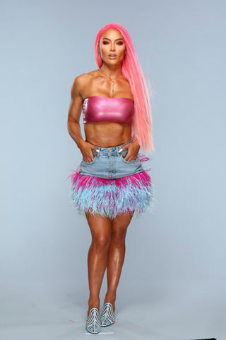 Woman posing with her hands on her hips, long pink hair, pink Vex tube top and a denim skirt smiling