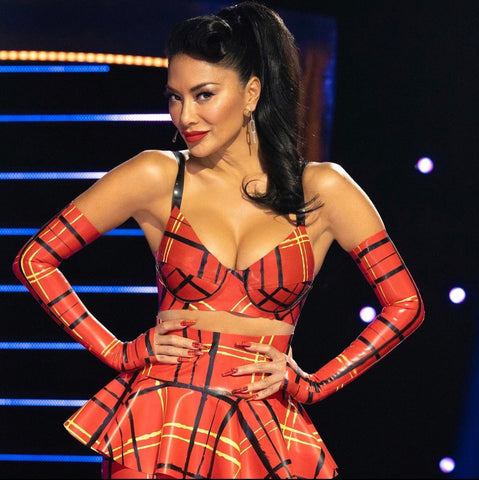 Nicole Scherzinger wearing a red, white and black plaid bra, skirt and gloves for the Masked Singer