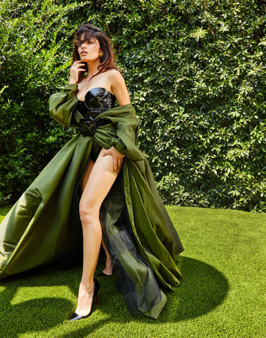 Woman wearing black Vex strapless Marilyn bodysuit and flowing green overcoat posing for an interview in Photobook Magazine