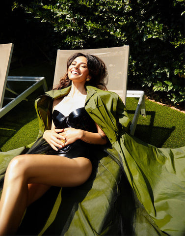 Woman wearing black Vex strapless Marilyn bodysuit lounging on a lawn chair for an interview in Photobook Magazine