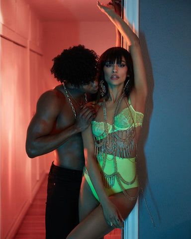 Actress wearing neon yellow Vex high waisted knickers and matching bra posing is a doorway while a male model stands behind her