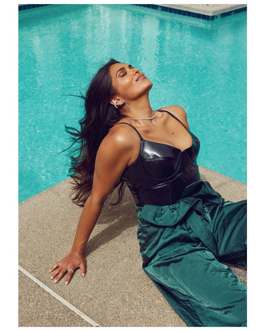 Woman wearing Vex's Underwire tank sitting by a pool with green pants featured in Vogue India