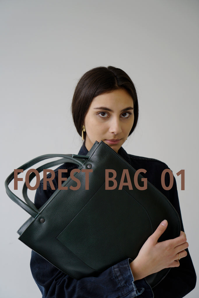 female model wearing a green Horween leather tote bag