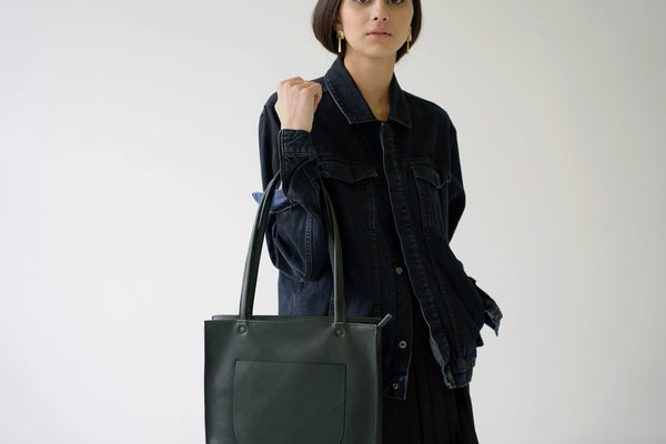 female model holding a leather tote bag