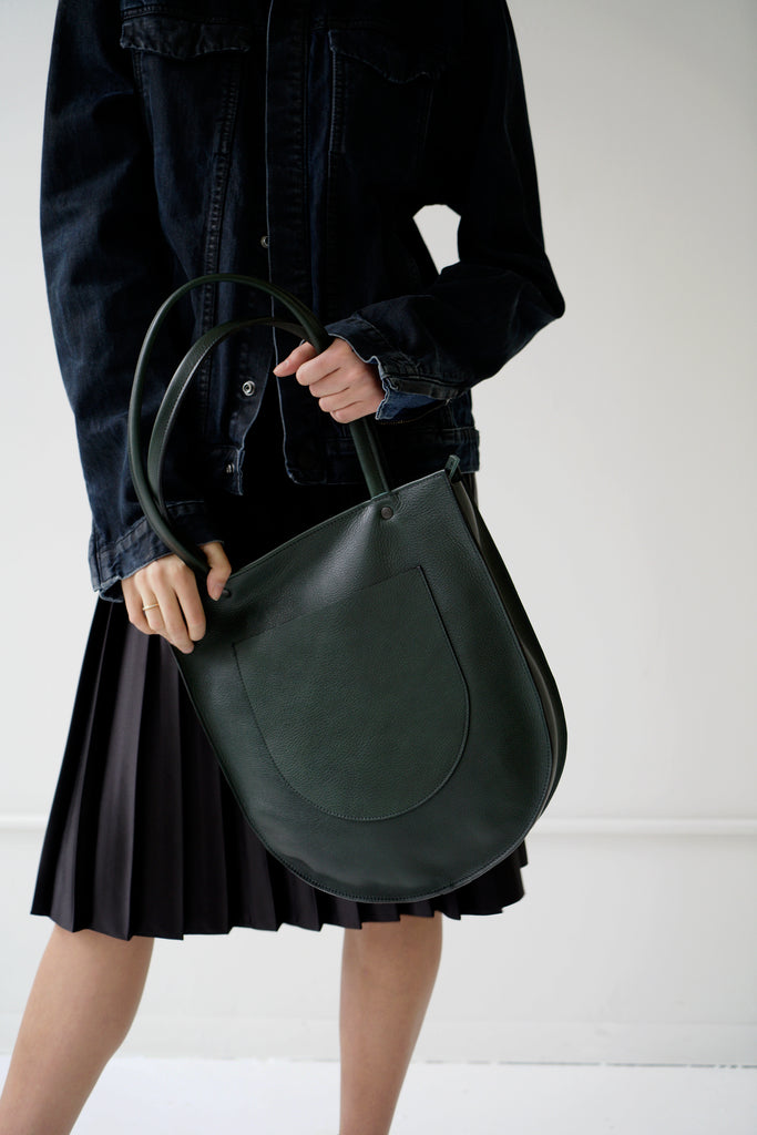 Female model with green leather bag