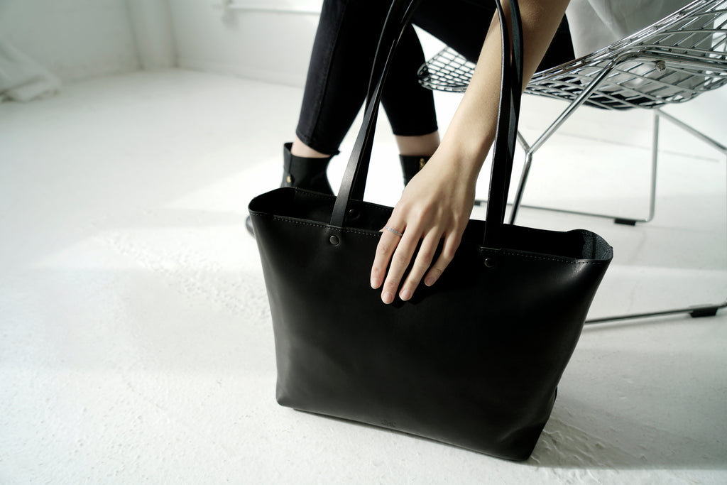 Large black leather tote sits next to female model
